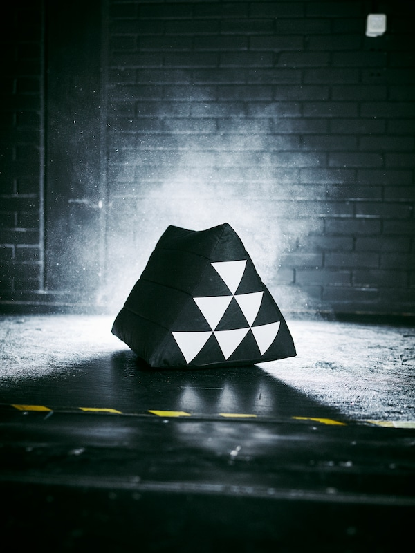 A triangular SAMMANKOPPLA cushion with a pattern of black and white triangles is standing on the floor in a dark room.