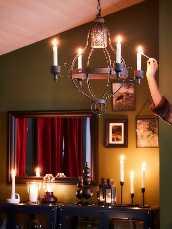 A woman's hand lights candles in a black chandelier, with more lit candles, two glass-door cabinets and a mirror behind.