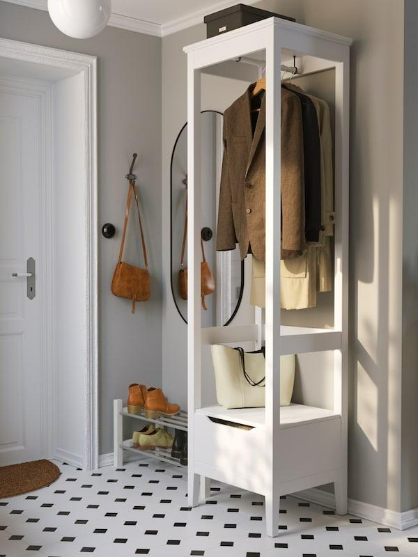 En un pasillo con baldosas blancas y negras hay un armario abierto IDANÄS blanco con varias chaquetas colgadas en perchas en su interior.