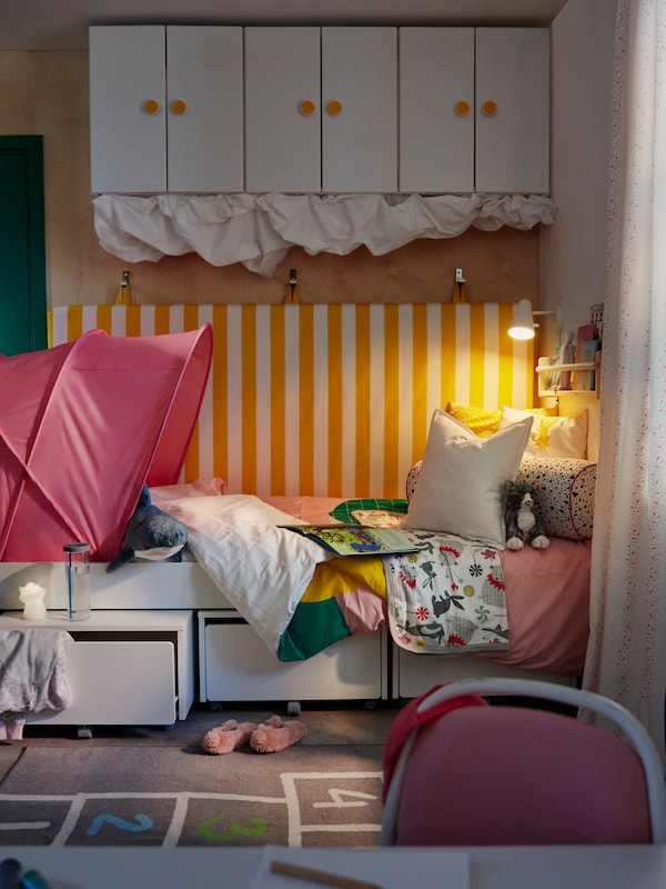 A child's room with a SLÄKT bed and storage boxes with a FUBBLA wall lamp at one end, and a SUFFLETT bed tent at the other.
