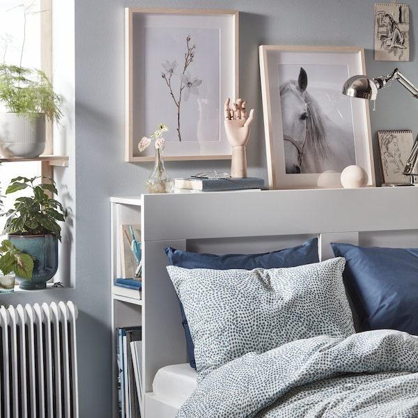 A bright white and blue bedroom with a white bedframe and patterned linens. Many decorative assessories are in the room, including a wooden hand, plants and artwork.