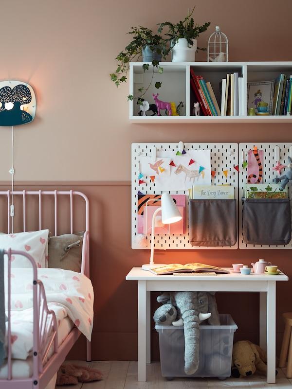 En lyserød udtræksseng med lamelbund, en hvid reol, hvide hulplader og bøger.