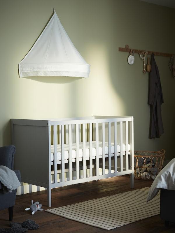 En grå tremmeseng, en hvid sengehimmel, et fladvævet tæppe med hvide og sorte striber og knagerækker af eg.