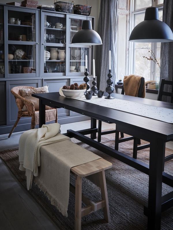 Deux bougeoirs noirs DEKORERA sont dressés sur une table noire dans un salon à l'ambiance rustique.