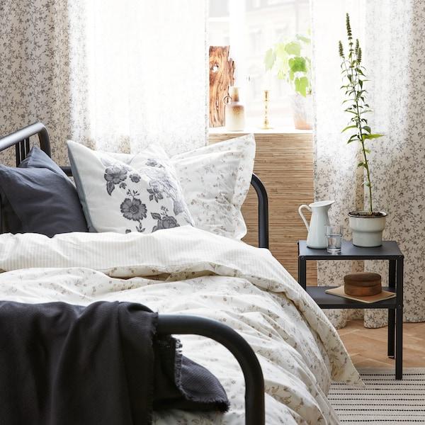 SOCKERÄRT vase on KNARREVIK nightstand in a bedroom. PRAKTBRÄCKA cushion on a bed.
