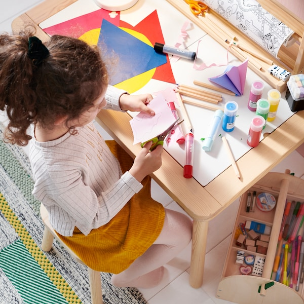 A girl sitting at FLISAT children's table on a FLISAT children's stool is crafting with MÅLA paint colours, paper and scissors.