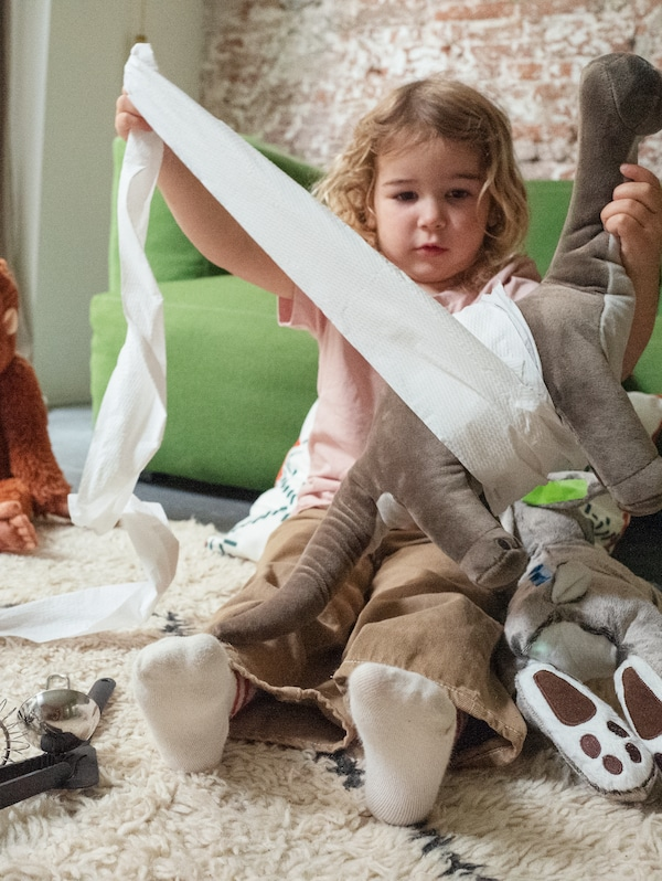 A girl sits in a living room using toilet paper to bandage a JÄTTELIK dinosaur.