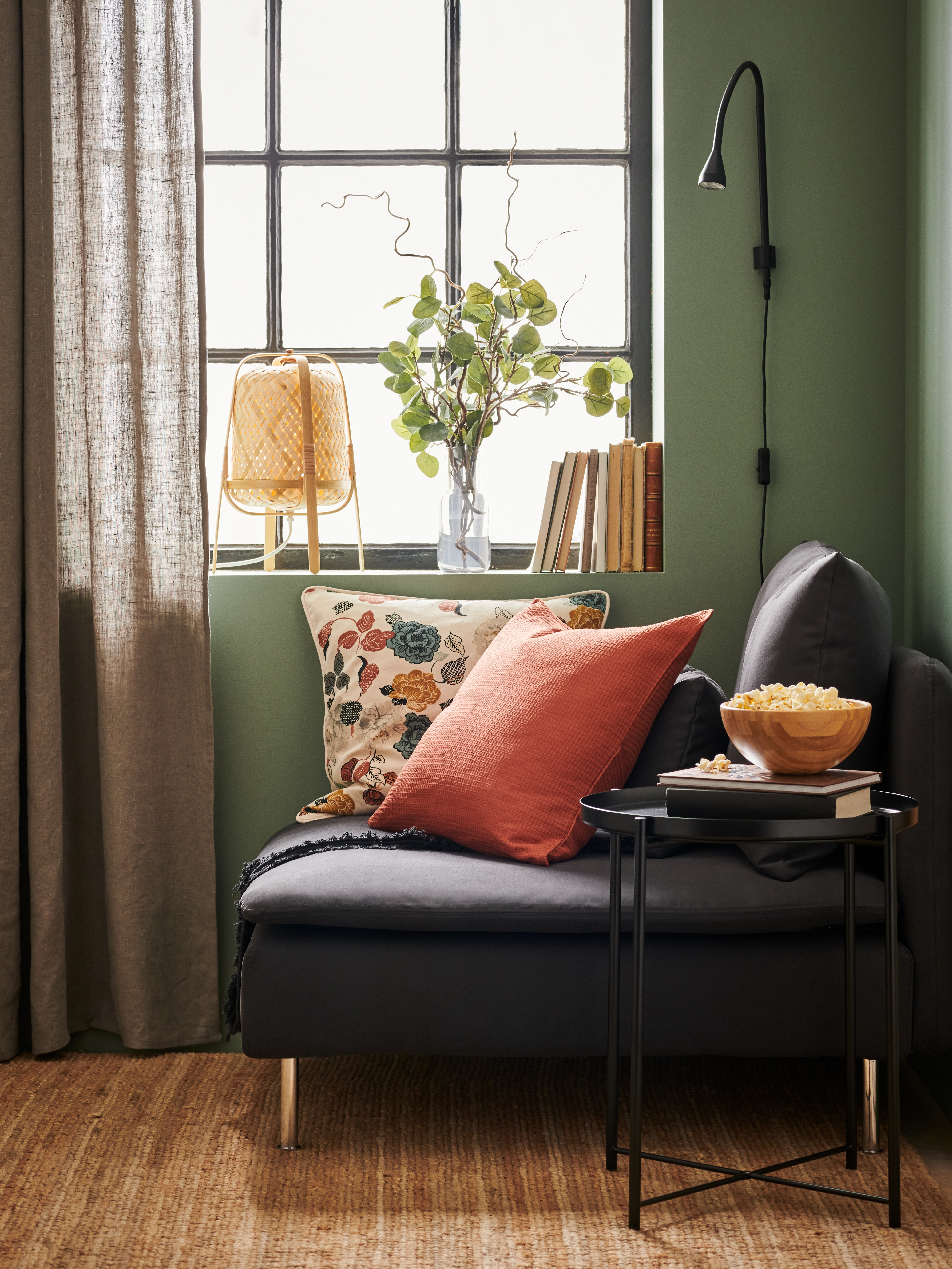 An armchair in a living-room corner. Cushions with EBBATILDA and TROLLMÅL covers, SMYCKA artificial leaves in a window above.