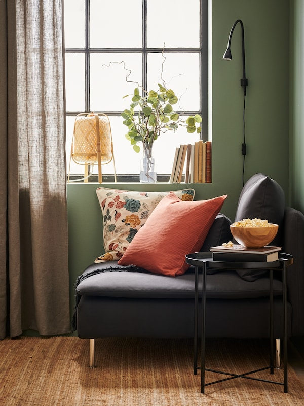 A corner of a living room with green walls, plants at the window, and cushions heaped on a small sofa.