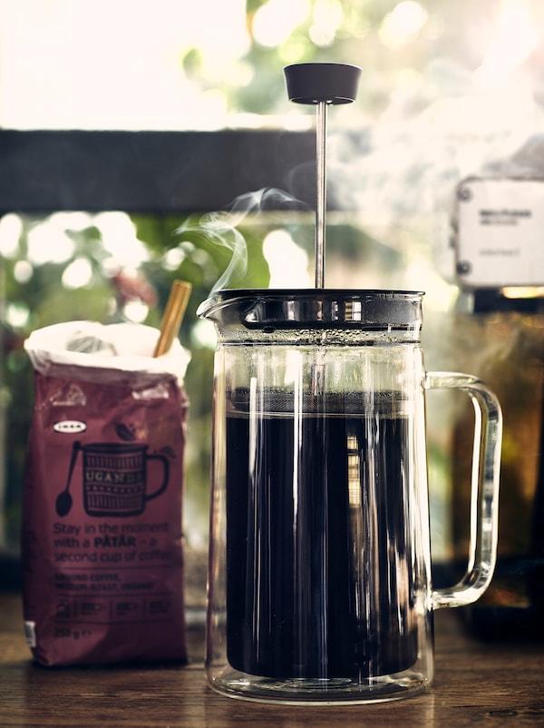 Eine offene Packung PÅTÅR Bio-Filterkaffee neben einem EGENTLIG Kaffee-/Teezubereiter, aus dem Dampf aufsteigt.