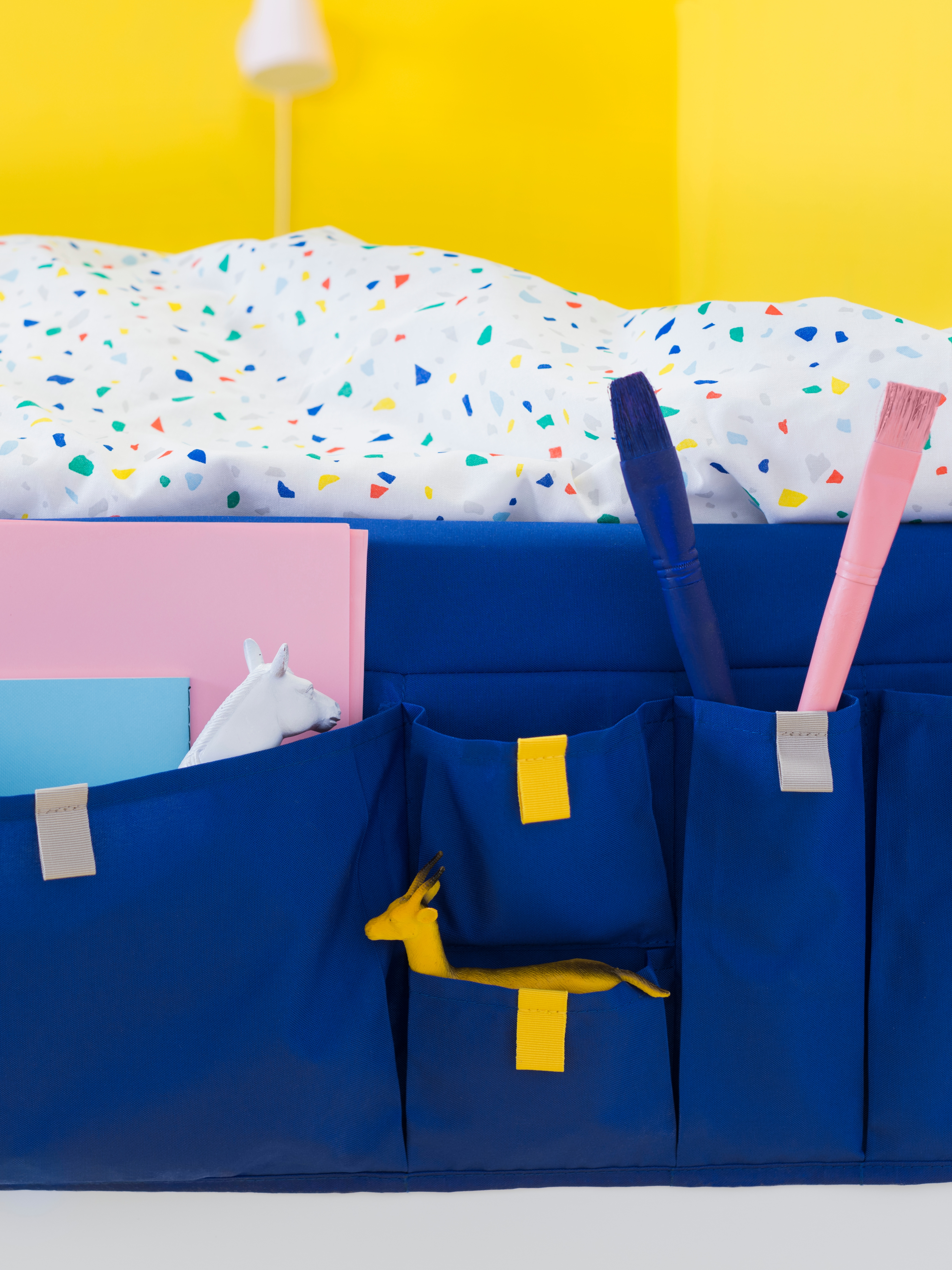 Close-up of a blue, fabric MÖJLIGHET bed pocket, with different-sized sections holding toy animals, paint brushes and paper.