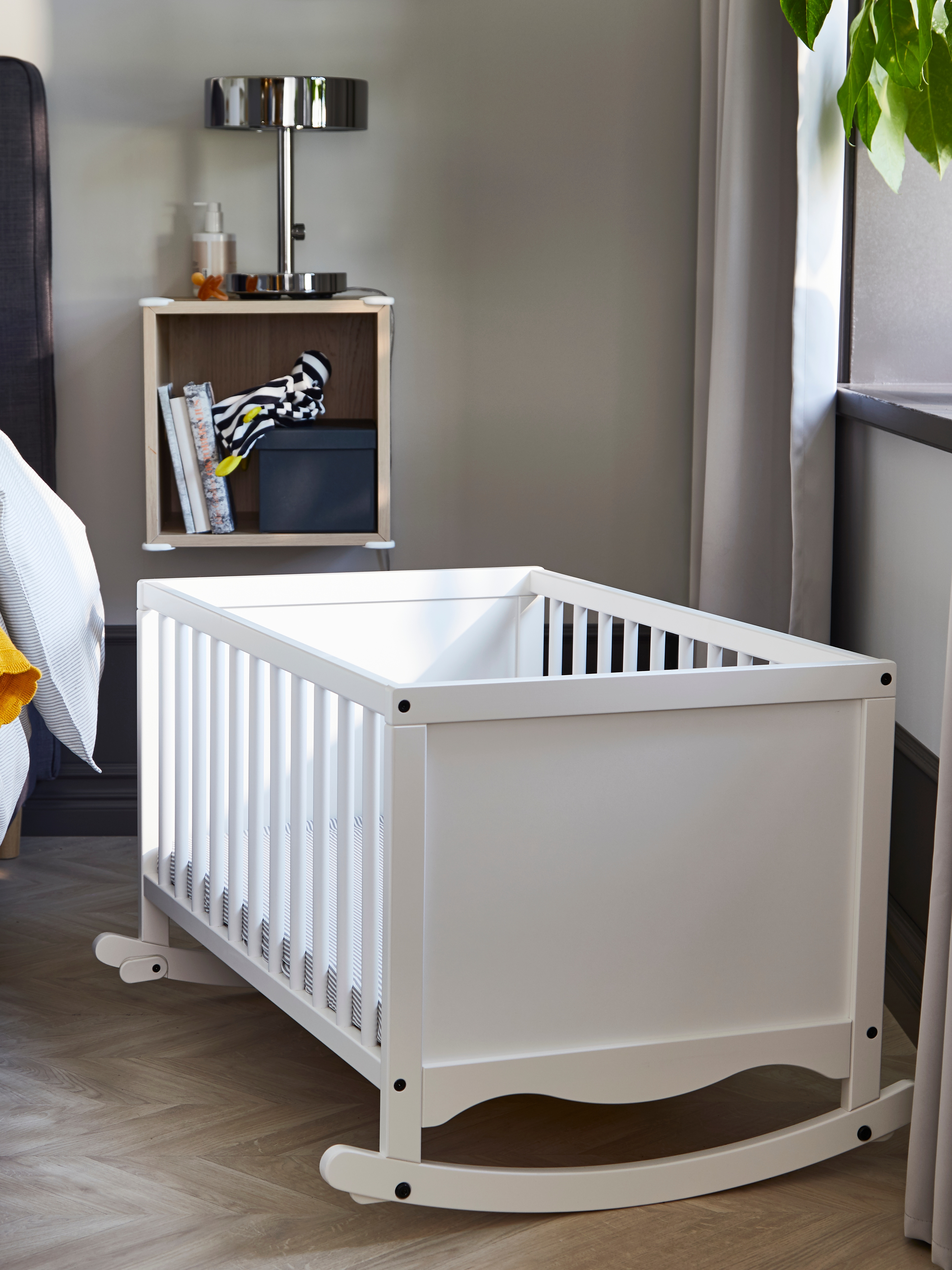 A white SOLGUL cradle with round spindled bars on two sides and curved rockers underneath sits between a bed and a window.