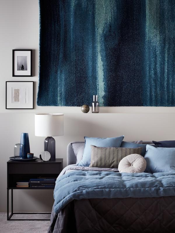 Egy szürke-bézs ÄNGSLILJA ágyneművel kiegészített fekete SAGSTUA ágyat, mellette fekete VIKHAMMER éjjeliszekrényt és TONVIS asztali lámpát, felettük pedig egy kék faliszőnyeget látunk.