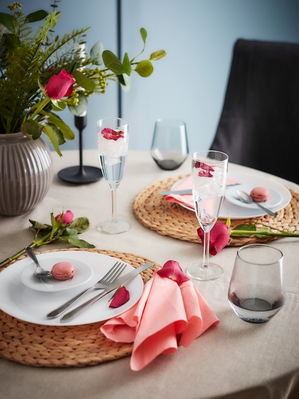 A table set for a dinner for two with  lots of pink accents