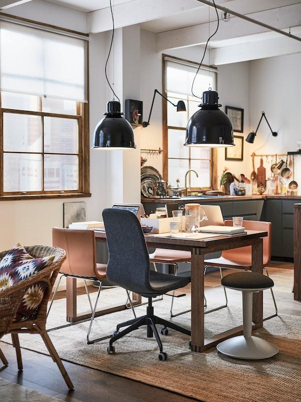 Une salle à manger transformée en espace de travail, avec un mélange bureau-chaise de salon autour d'une table à manger MÖRBYLÅNGA.