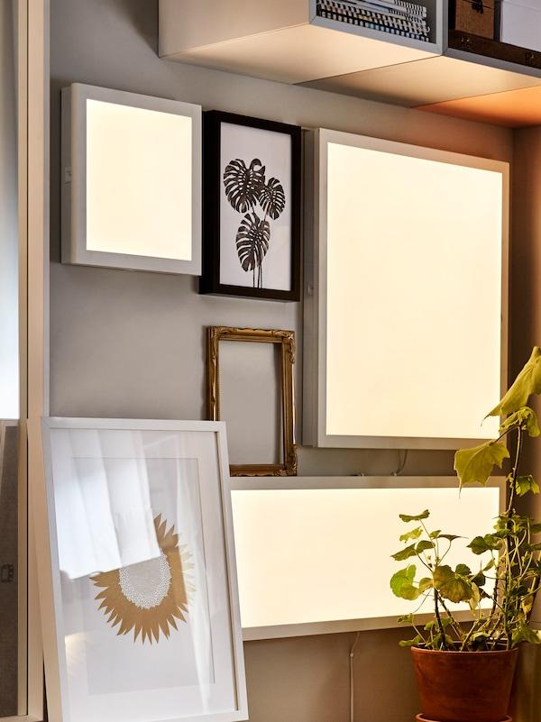 Různé osvětlovací panely LED FLOALT namontované na stěně. Na stěně visí také několik rámů sobrázky, další se ostěnu opírají.