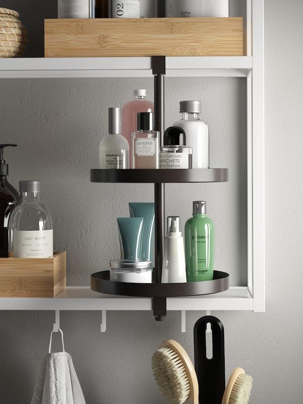 Un estante branco montado na parede e un andel xiratorio de mesma cor con botellas de vidro e outros artigos de baño.