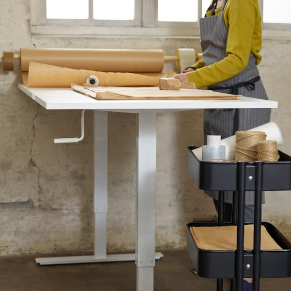A person standing by a white work desk, adjusting some rolls of brown work materials, a black trolley close by.
