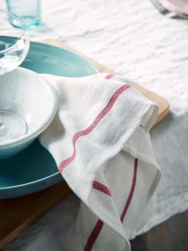 A white TEKLA tea towel with a red stripe is draped over a light green ENTYDIG bowl on a table with a white tablecloth.