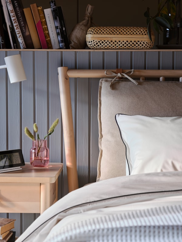 The corner of a BJÖRKSNÄS bed, in front of a wooden wall with built-in bookshelf and next to a bedside table.