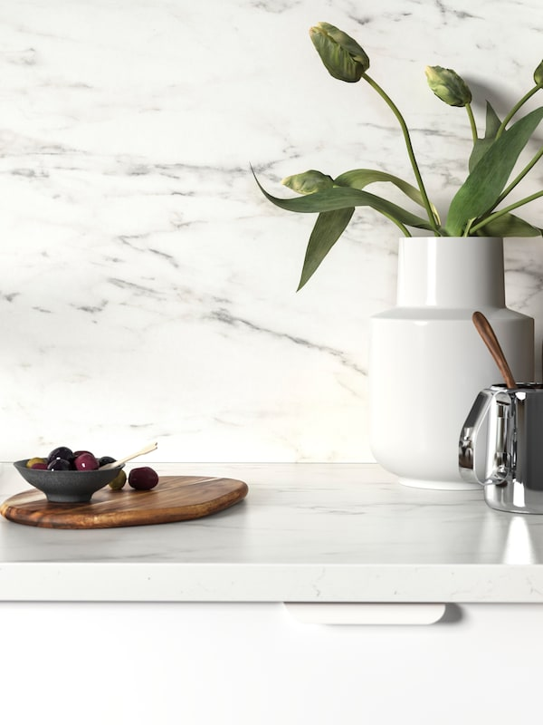 A white EKBACKEN worktop with marble effect, olives on a wooden chopping board, and a white vase with tulips on top.