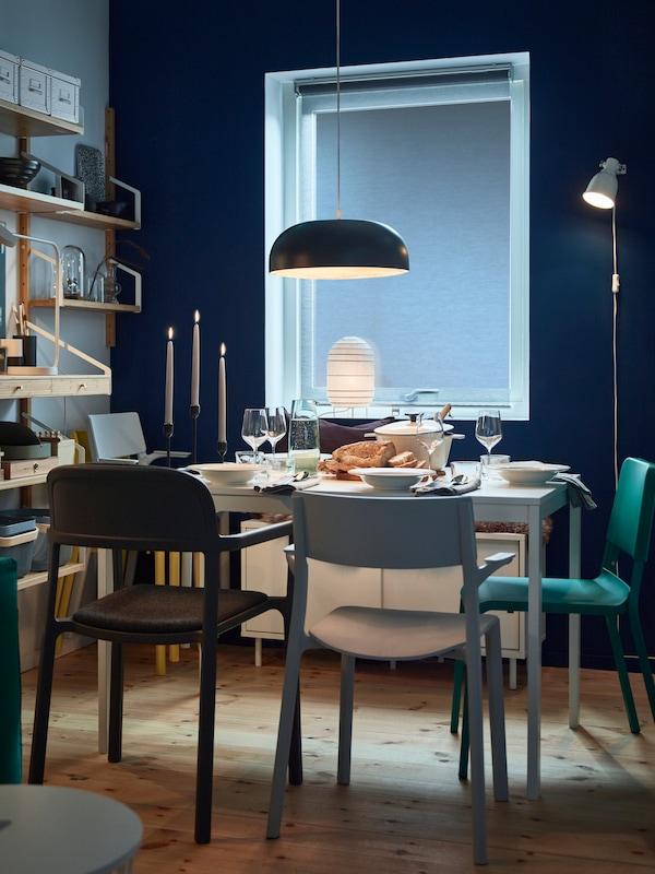 Salle à manger faiblement éclairée. Mélange de différents types de chaises placées autour d'une table