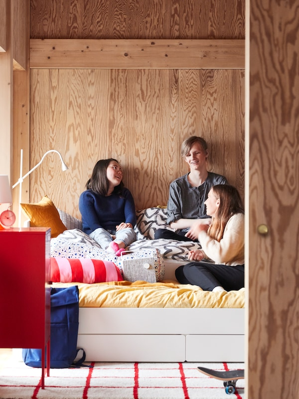 Three teenagers sitting on a SLÄKT bed with underbed and storage, covered with PUDERVIVA bed linen and MÖJLIGHET cushions.