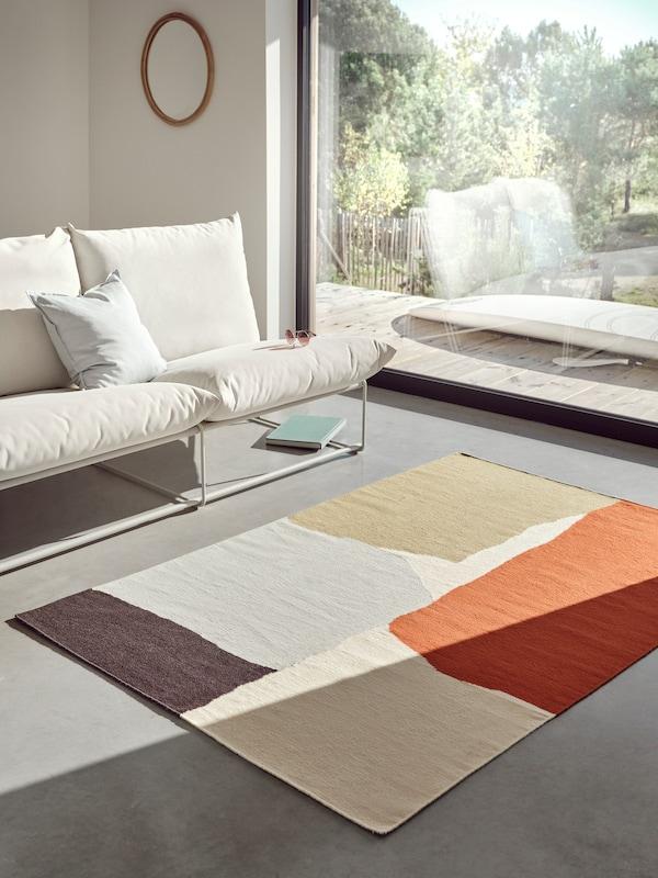 TVINGSTRUP multifärgad matta i ull ligger på ett betonggolv i ett ljust och fräsch vardagsrum.