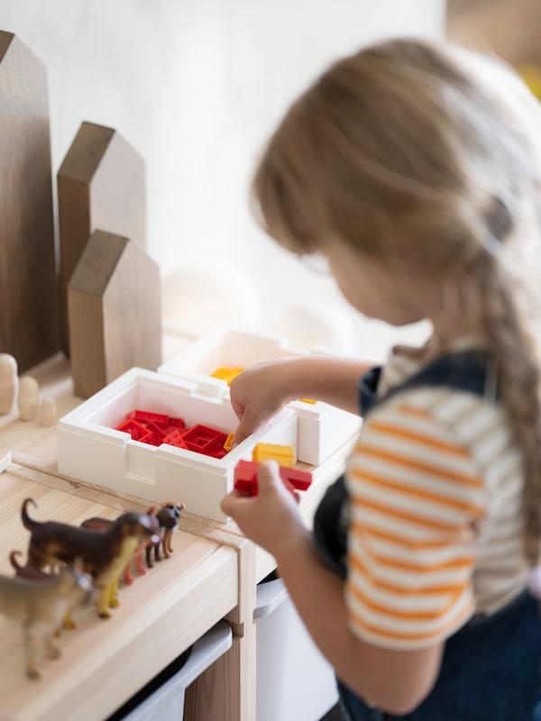 子どもが、TROFAST/トロファスト 収納コンビネーションの上に置いたBYGGLEK/ビッグレク LEGO®ボックス ふた付きの中にBYGGLEK/ビッグレク LEGO®ブロックを入れている。