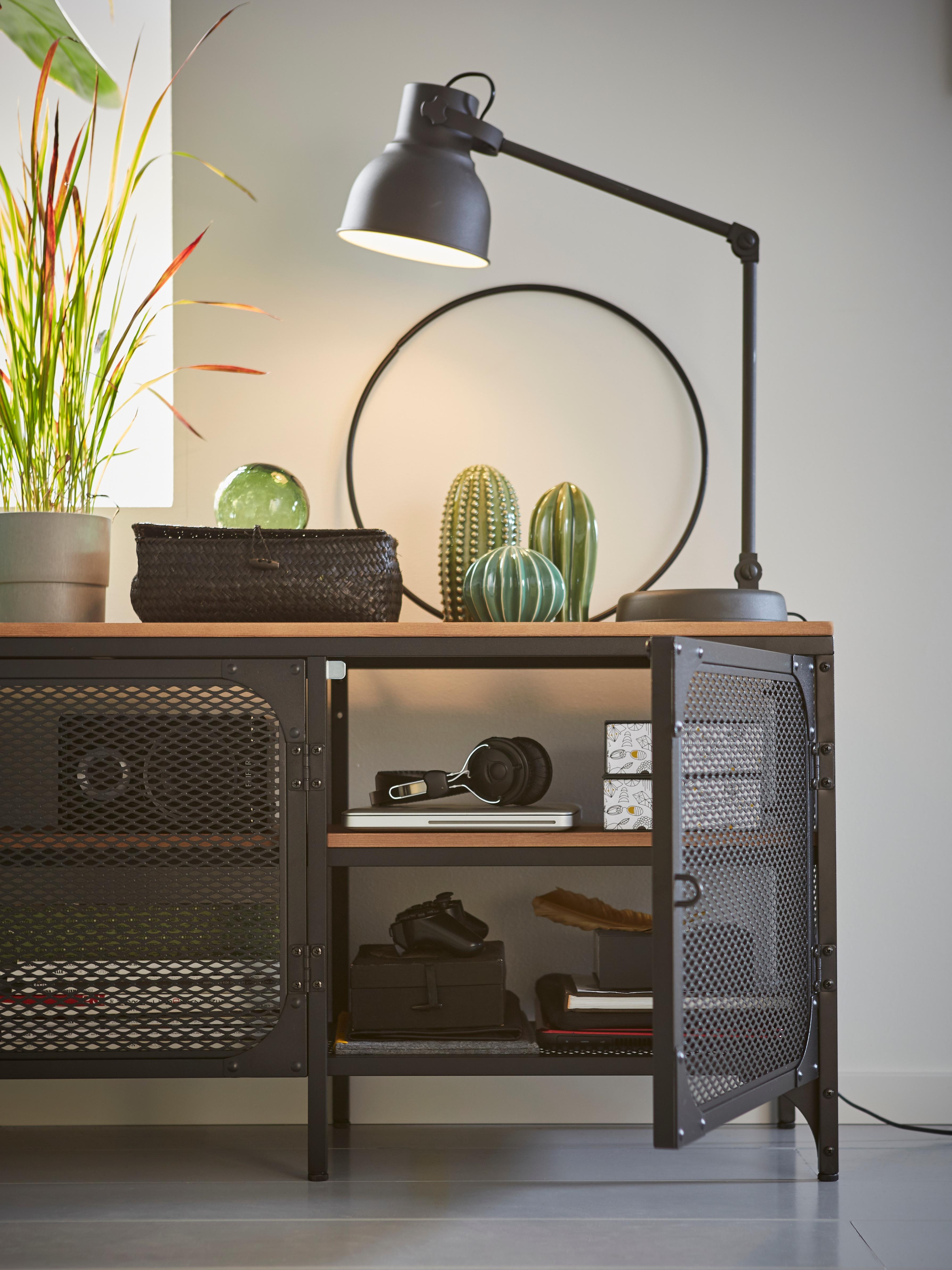 Crna FJÄLLBO TV klupa s metalnim mrežastim vratima i pločom od punog drveta bora u kojoj su kutije i knjige s lampom i dekorom na vrhu.