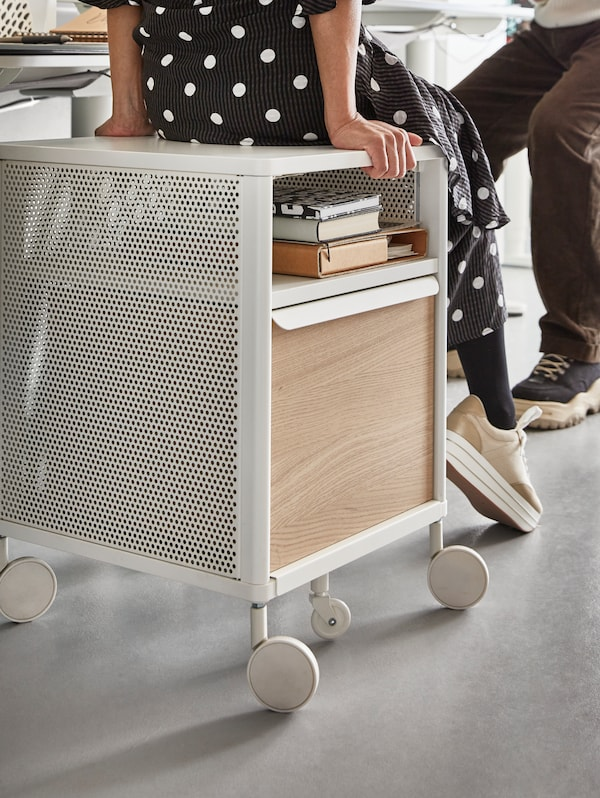 A storage unit with a woman sitting on it, and another person facing her, books and files in the storage unit.