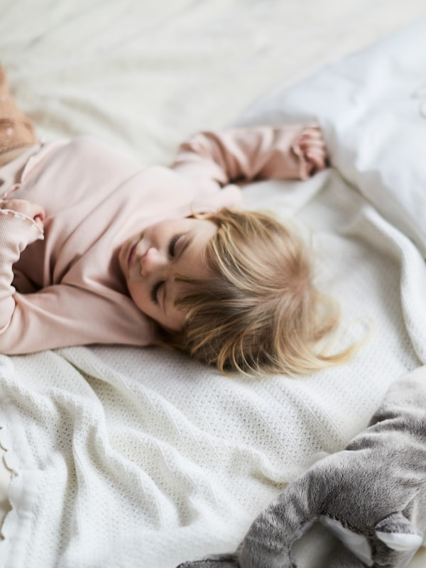 A young child with blonde hair wearing a pink jumper lies sleeping on a GULSPARV blanket on top of a bed.