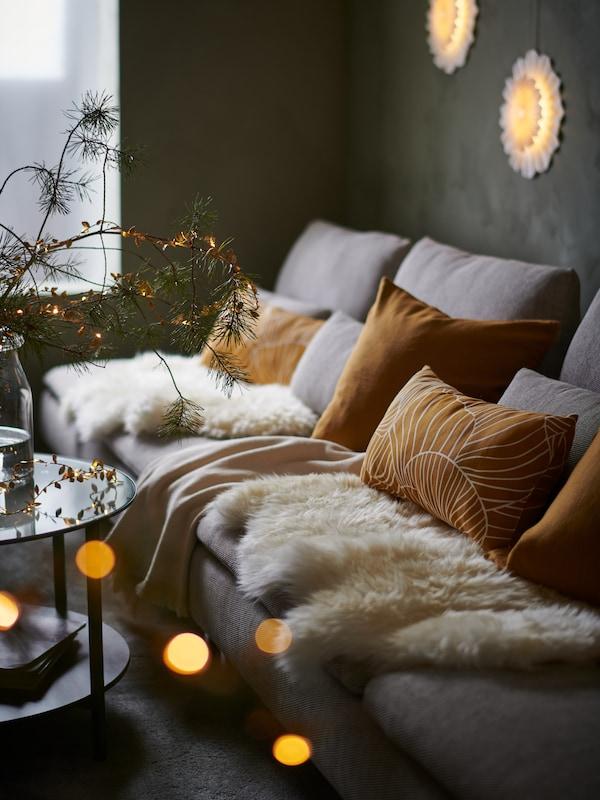 dans un salon, focus sur un canapé avec des coussins couleur ocre, des plaids et des luminaires à la lumière chaleureuse
