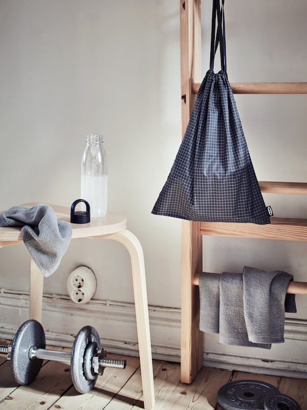 An area along the side of a room scattered with weights, an IKEA 365+ water bottle, KORNAN washcloths, and a RENSARE gym bag.