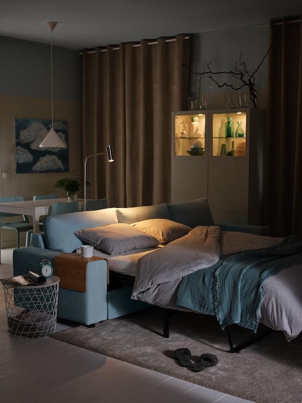 3-pers. sovesofa med chaiselong redt op som seng, en gulv-/læselampe og et sengesæt.