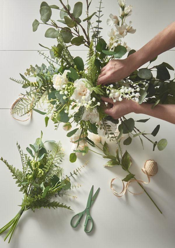 A display of flowers being worked on by a pair of hands, with scissors and ribbon used to make a bouquet.