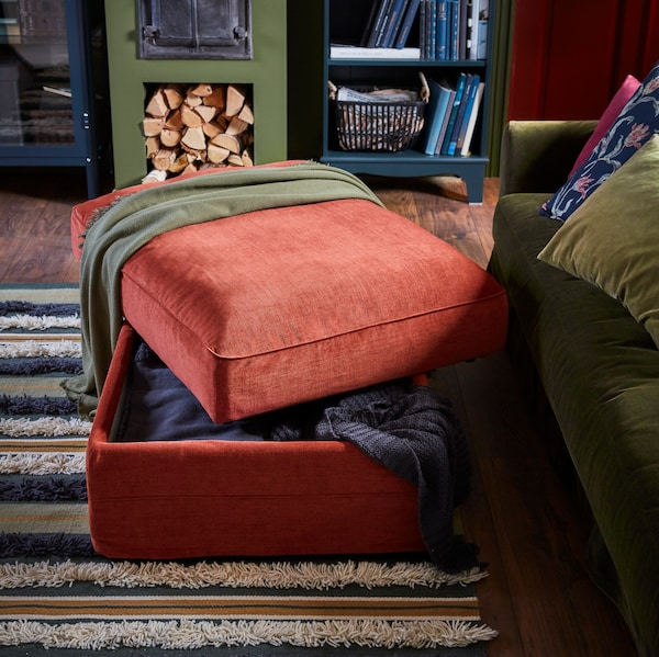An opened footstool with storage standing on a rug with a green throw over it, and the edge of a green sofa with cushions.