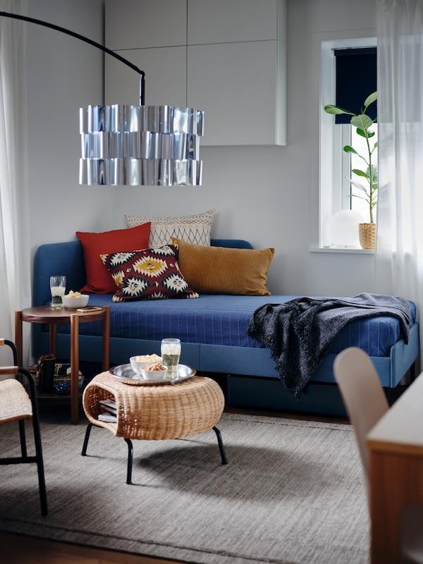 Polstret sengestel med hjørnegavl, et blåt sengetæppe, farvestrålende puder og en puf med opbevaring med snacks.