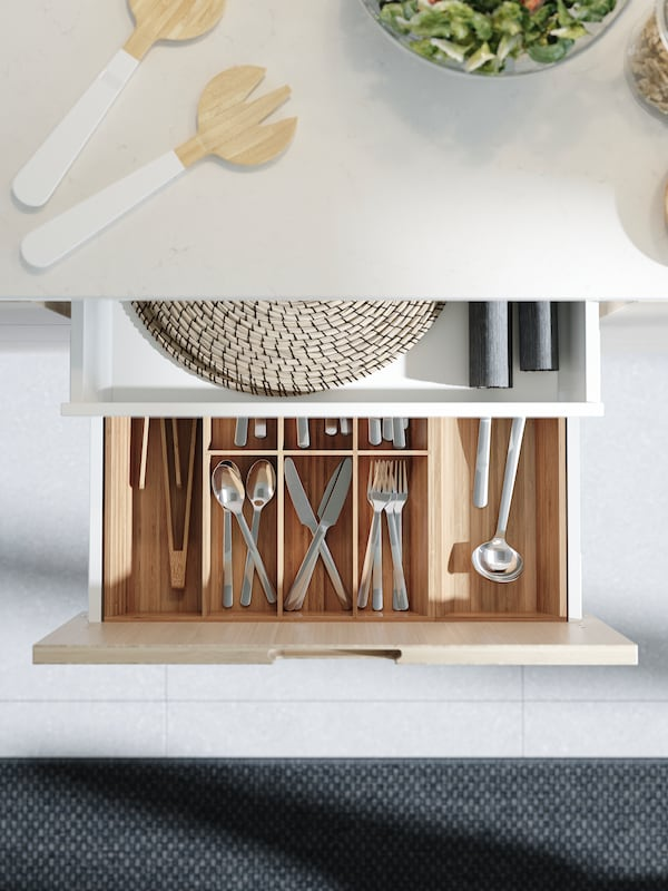 An open kitchen drawer with a cutlery tray in bamboo. Cutlery and different kitchen utensils are stored and divided here.