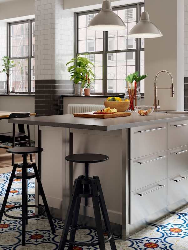 An industrial style kitchen with large windows and mosaic floors, two black DALFRED bar stools by a kitchen island.