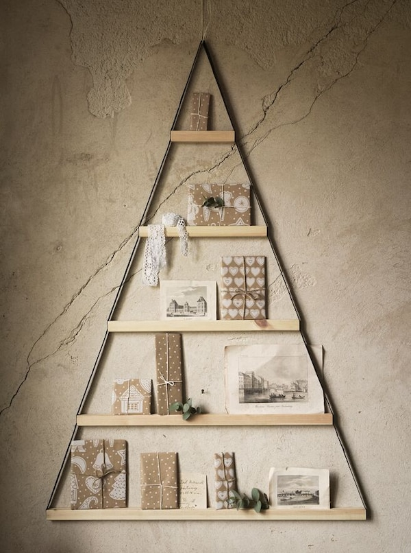 A wooden VINTER 2020 wall decoration in the shape of a triangle hangs on a wall, with presents leaned on its rungs.