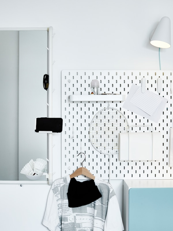 A white SKÅDIS pegboard with accessories is attached to the wall beside a MÖJLIGHET mirror which holds a mobile phone.