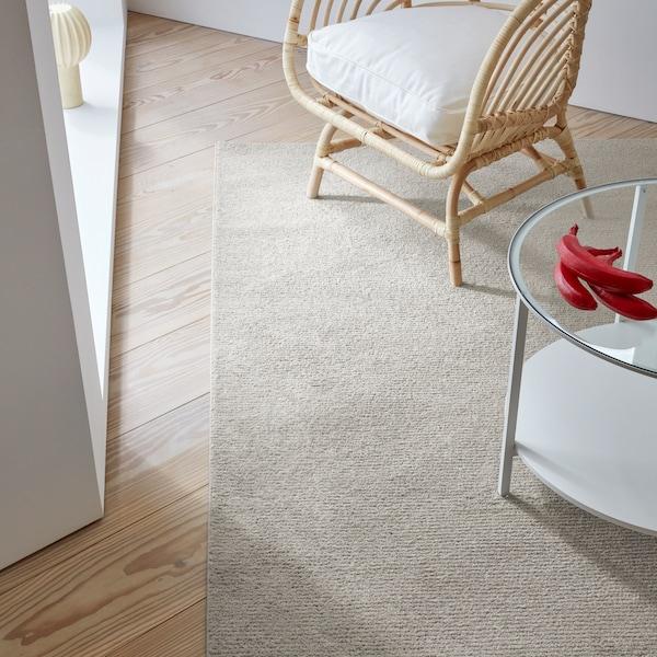 Un tappeto chiaro, una poltrona in rattan con un cuscino bianco e un tavolino con piano tavolo in vetro - IKEA