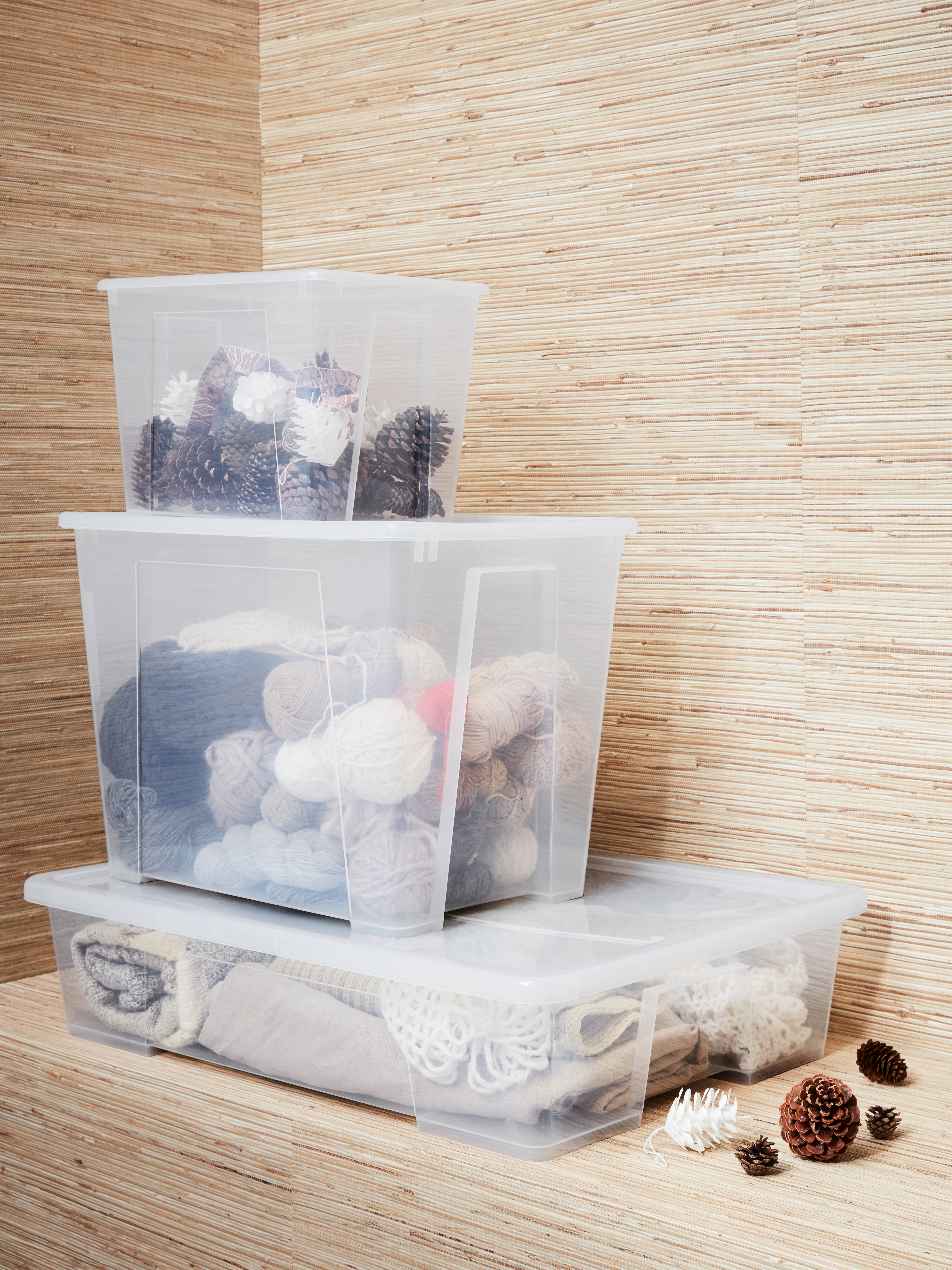 Close-up view of storage cabinet, with three transparent plastic boxes with lids, cones, knitting utensils and knitwear.