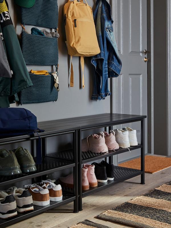 Dous bancos PINNIG con almacenaxe para zapatos, con zapatos e botas, nunha entrada. Enriba hai almacenaxe para pendurar NORDRANA.
