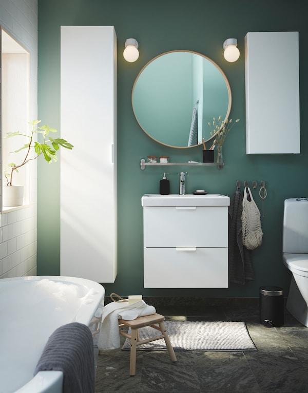 خزانة بمرآة على جدار مكسو ببلاط أبيض/ورق جدران ذهبية/بنية وحوض غسل أبيض مع درجين وخزانة بيضاء عالية.