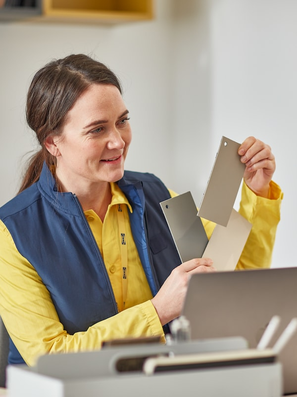 A woman in blue-and-yellow IKEA co-worker clothes holds up colour samples while looking across the desk she's sitting at.