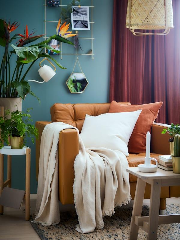 Ruosteen värinen lepotuoli tummanturkoosin sävyisessä huoneessa. Lepotuolin päällä valkoinen huopa ja koristetyyny.