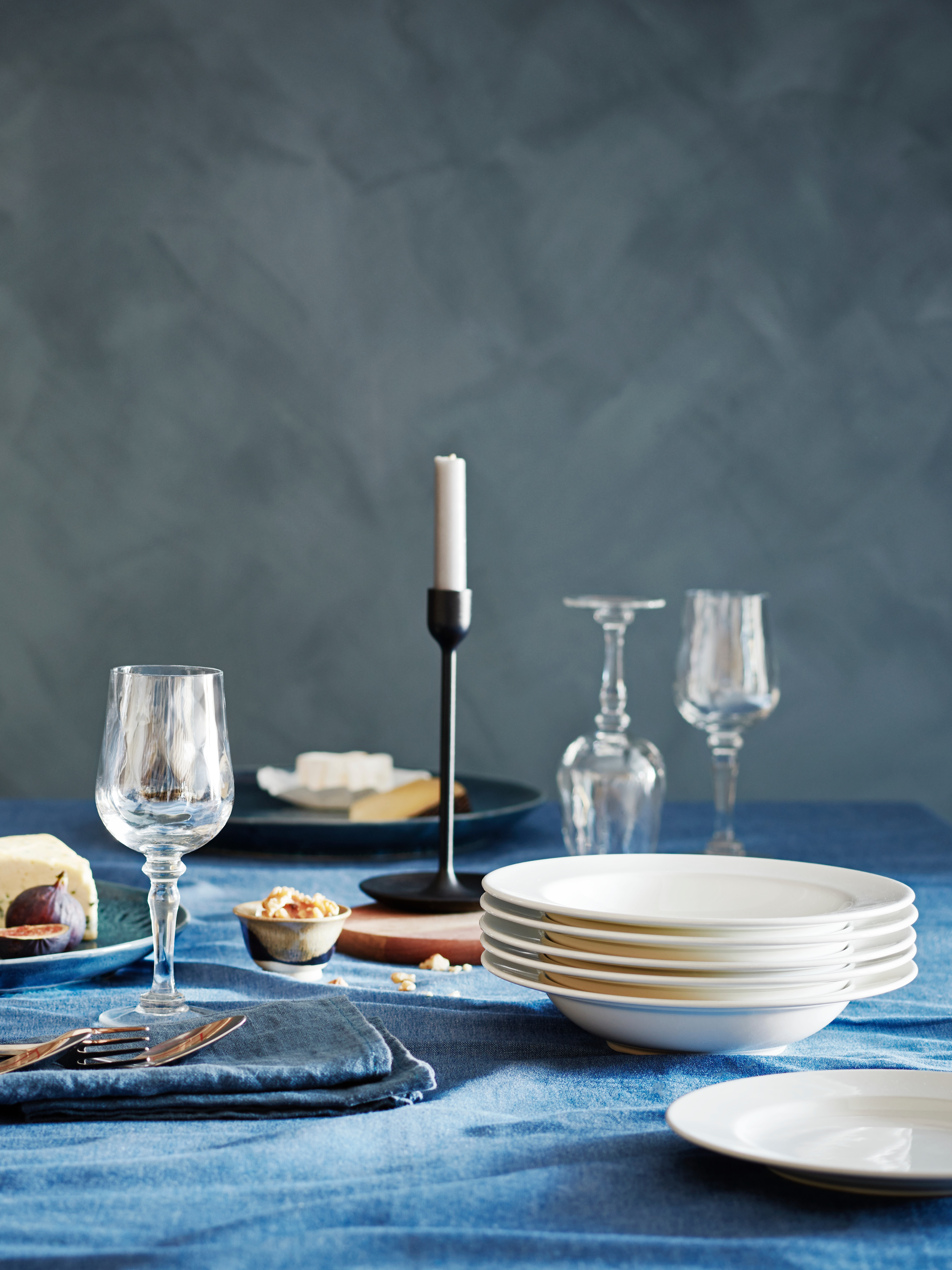 A dinner table with cheese and figs, a blue SEVÄRD tablecloth, VARDAGEN deep white plates and KONUNGSLIG champagne glasses.
