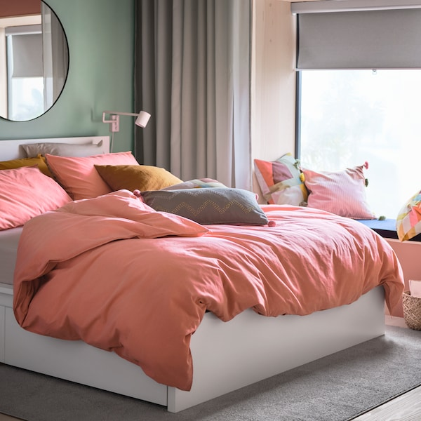 A MALM bed with storage and with ÄNGSLILJA light brown-red bed linen stands under a wall-mounted LINDBYN mirror.